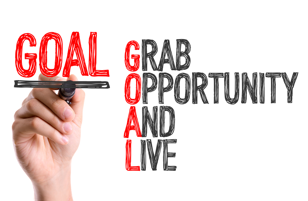 Hand with marker writing the word Goal Acronym